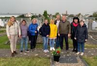 Vēstniecības darbinieki un luterāņu draudzes cilvēki sakopj K.Pētersona kapa vietu